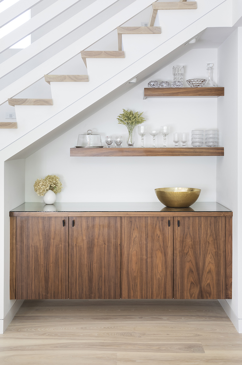 This custom built-in buffet creatively uses the space under the staircase as a focal point to the dining room area. AMEK