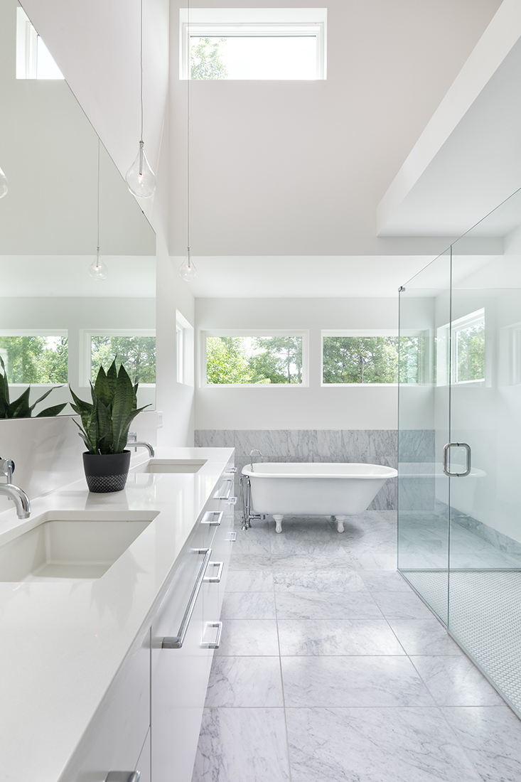 A vintage free-standing soaking tub is the centerpiece for this bright master bathroom. AMEK